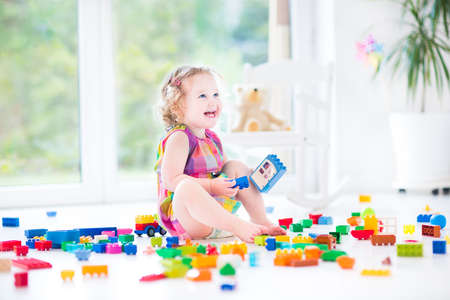 Photo pour Adorable laughing toddler girl playing with colorful blocks sitting on a floor in a sunny bedroom with a big window   - image libre de droit