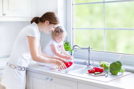 Foto de Young mother and her funny curly toddler daughter washing vegetables together in a kitchen sink getting ready to make salad for lunch in a sunny white kitchen with a big garden view window   - Imagen libre de derechos
