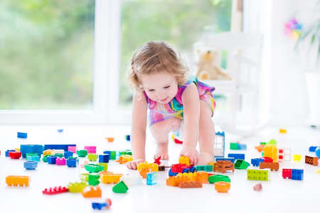 Photo pour Beautiful toddler girl with curly hair sitting on a floor in a toy mess in a sunny white bedroom with big windows with garden view playing with colorful construction blocks   - image libre de droit