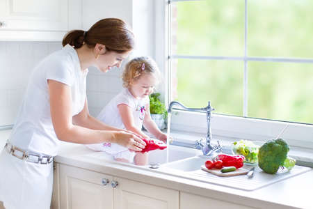 Foto de Young beautiful mother and her cute curly toddler daughter washing vegetables together in a kitchen sink getting ready to cook salad for lunch in a sunny white kitchen with a big garden view window   - Imagen libre de derechos