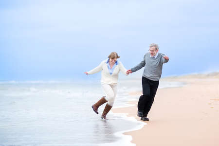 Photo for Happy middle aged couple running on a beach holding hands and jumping away from the waves   - Royalty Free Image