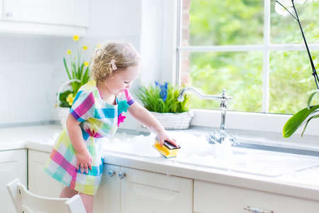 Foto de Cute curly toddler girl in a colorful dress washing dishes, cleaning with a sponge and playing with foam in the sink in a beautiful sunny white kitchen with a garden view window in a modern home - Imagen libre de derechos