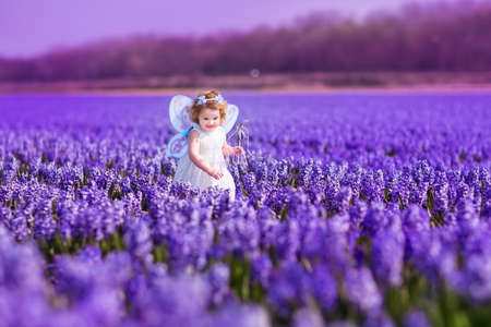 Foto de Portrait of an adorable toddler girl in a magic fairy costume and flower crown in her curly hair playing with a wand in a beautiful field of purple hyacinths in Keukenhof, Holland on windy spring day - Imagen libre de derechos
