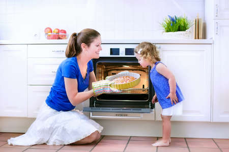 Photo pour Young happy mother and her adorable curly toddler daughter wearing blue dress baking a pie together in an oven in a white sunny kitchen with modern appliances and devices - image libre de droit