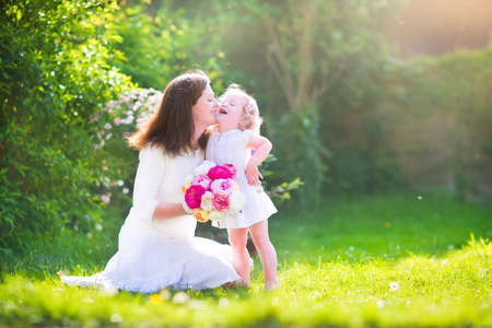 Foto de Beautiful young mother nd her adorable little daughter, cute little curly girl in a white dress, playing in the garden, hugging and kissing, with a bunch of red and pink flowers on a sunny summer day - Imagen libre de derechos