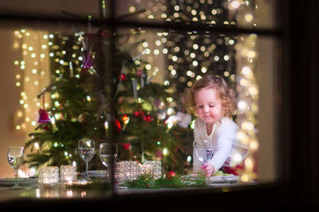 Photo pour Cute curly toddler girl standing at a Christmas dinner table settling the glasses and dishes preparing to celebrate Xmas Eve, view through a window from outside into a decorated dining room with tree and lights - image libre de droit