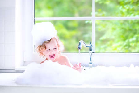 Photo pour Funny little baby girl with wet curly hair taking a bath in a kitchen sink with lots of foam playing with water drops and splashes next to a big window with garden view - image libre de droit