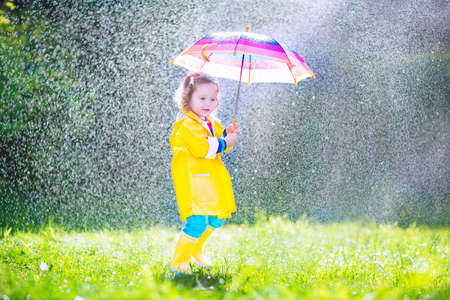 Funny cute curly toddler girl wearing yellow waterproof coat and boots holding colorful umbrella playing in the garden by rain and sun weather on a warm autumn or sumemr day