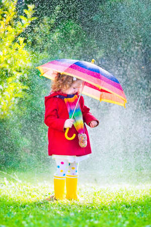 Funny cute curly toddler girl wearing red waterproof coat and yellow rubber boots holding colorful umbrella playing in the garden by rain and sun weather on a warm autumn or summer day