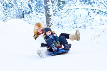 Photo for Young happy mother and her adorable son having fun together on a sleigh ride in a snowy park - Royalty Free Image