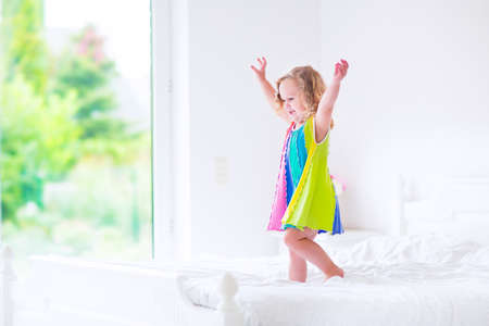 Foto de Cute little curly toddler girl in a colorful dress jumping on a big white bed laughing and having fun on a sunny weekend morning in a bedroom - Imagen libre de derechos