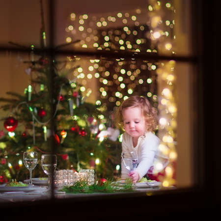 Photo for Cute curly toddler girl standing at a Christmas dinner table settling the dishes preparing to celebrate Xmas Eve, view through a window from outside into a decorated dining room with tree and lights - Royalty Free Image