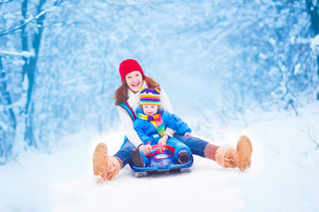 Foto de Young happy mother and her little toddler daughter enjoying a sledge ride in a beautiful snowy winter park - Imagen libre de derechos