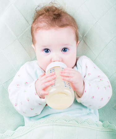 Photo for Beautiful little baby with a milk bottle under a warm knitted bl - Royalty Free Image