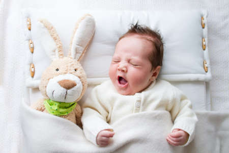 Photo pour Adorable sleepy newborn baby with a toy bunny yawning in bed - image libre de droit