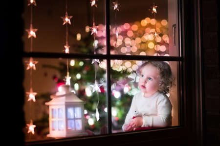 Photo pour Cute curly toddler girl sitting with a toy bear at home during Xhristmas time, preparing to celebrate Xmas Eve, view through a window from outside into a decorated dining room with tree and lights - image libre de droit