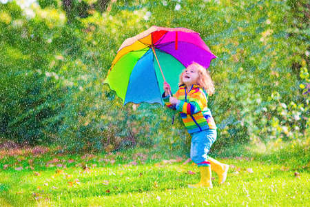 Funny cute curly toddler girl wearing yellow waterproof coat and boots holding colorful umbrella playing in the garden by rain and sun weather on a warm autumn or summer day