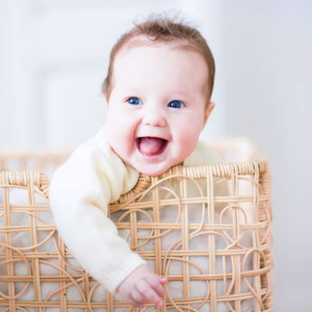 Foto de Adorable laughing baby sitting in a laundry basket - Imagen libre de derechos