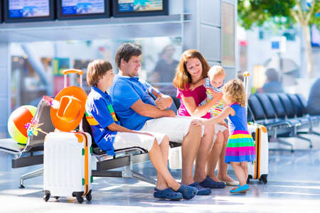 Foto de Big happy family with three kids traveling by airplane at Dusseldorf International airport, parents with teenager boy, toddler girl and little baby holding colorful luggage for summer beach vacation - Imagen libre de derechos