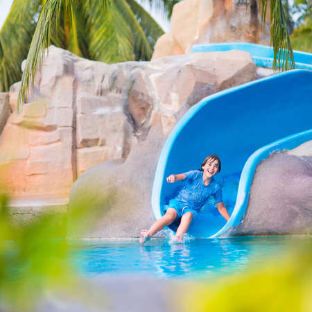 Photo for Happy boy on water slide in a swimming pool having fun during summer vacation in a beautiful tropical resort - Royalty Free Image