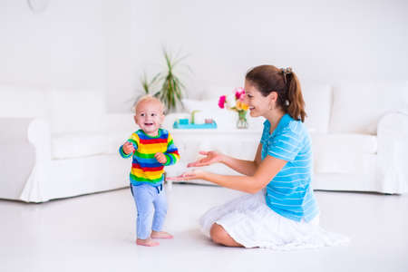 Photo pour Cute little baby boy making his first steps, walking to his mother in a white sunny living room - image libre de droit