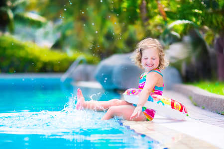 Foto de Adorable little girl with curly hair wearing a colorful swimming suit playing with water splashes at beautiful pool in a tropical resort having fun during family summer vacation - Imagen libre de derechos