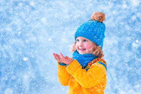 Foto de Adorable little girl, cute toddler in a blue knitted hat and yellow nordic sweater, playing with snow catching snowflakes having fun outdoors in a beautiful winter park - Imagen libre de derechos