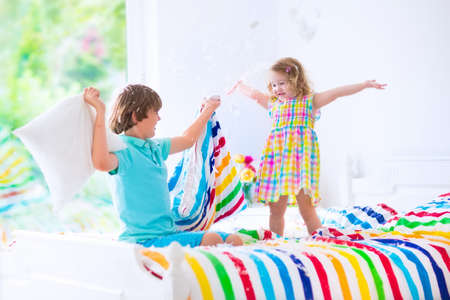 Photo pour happy laughing boy and cute curly little girl having fun at pillow fight with feathers in the air jumping, laughing and giggling in a white bedroom with colorful bedding - image libre de droit