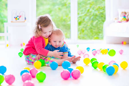 Photo pour cute curly toddler girl and a funny baby boy playing together with colorful balls in a white sunny room with big window - image libre de droit
