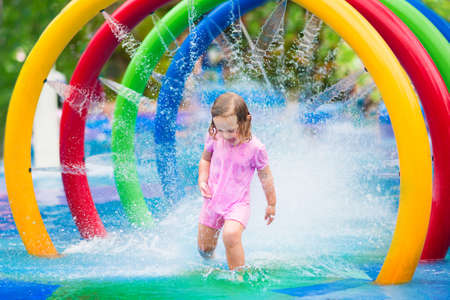 Foto de Happy little toddler girl running through a fountain having fun with water splashes in a swimming pool enjoying day trip to an aqua amusement park during summer family vacation - Imagen libre de derechos