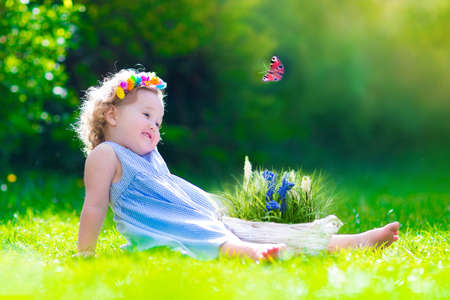 Foto de Cute little toddler girl with curly hair wearing a blue summer dress having fun watching a butterfly and flowers, relaxing in the garden on a sunny spring day - Imagen libre de derechos