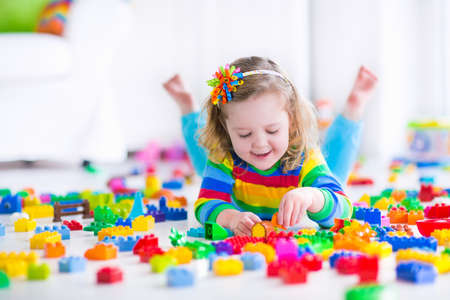 Photo for Cute funny preschooler little girl in a colorful shirt playing with construction toy blocks building a tower in a sunny kindergarten room - Royalty Free Image
