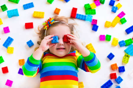 Foto de Cute funny preschooler little girl in a colorful shirt playing with construction toy blocks building a tower in a sunny kindergarten room - Imagen libre de derechos