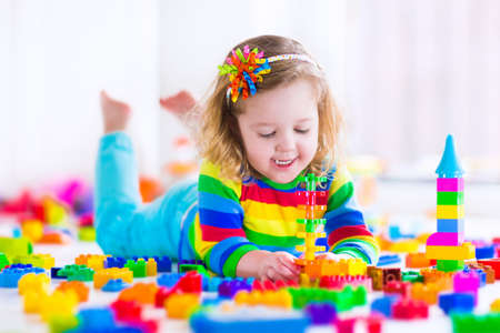 Photo pour Cute funny preschooler little girl in a colorful shirt playing with construction toy blocks building a tower in a sunny kindergarten room - image libre de droit