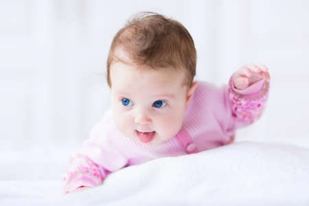 Photo pour Cute funny baby girl in a pink cardigan having fun learning to crawl - image libre de droit
