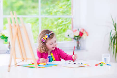 Photo pour Cute happy little girl, adorable preschooler, painting with water color on canvas standing on a wooden easel in a sunny white room at home or elementary school, creative young artist at work - image libre de droit
