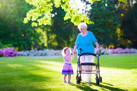 Photo pour Happy senior lady with a walker or wheel chair and a little toddler girl, grandmother and granddaughter, enjoying a walk in the park. Child supporting disabled grandparent. - image libre de droit