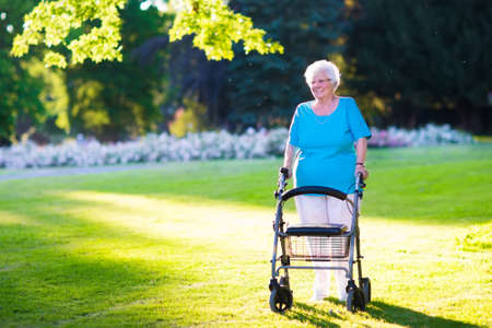 Photo pour Happy senior handicapped lady with a walking disability enjoying a walk in a sunny park pushing her walker or wheel chair, aid and support during retirement concept. - image libre de droit