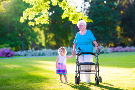 Foto de Happy senior lady with a walker or wheel chair and a little toddler girl, grandmother and granddaughter, enjoying a walk in the park. Child supporting disabled grandparent. - Imagen libre de derechos