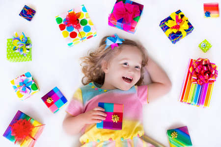 Photo for Happy laughing little girl, adorable toddler in a colorful party dress, holding many birthday presents, opening boxes decorated with ribbon and bow, excited to celebrate a family holiday - Royalty Free Image
