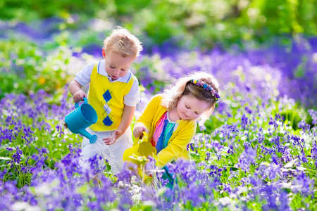 Foto de Kids gardening. Children playing  outdoors. Little girl and baby boy, brother and sister, working in the garden, planting flowers, watering flower bed. Family fun in summer. - Imagen libre de derechos