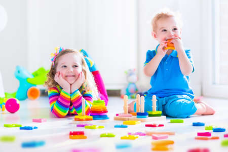 Photo pour Kids playing with wooden toys. Two children, cute toddler girl and funny baby boy, playing with toy blocks, building towers at home or day care. Educational child toys for preschool and kindergarten. - image libre de droit