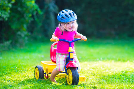 Photo pour Children riding a bike. Kids enjoying a bicycle ride. Little preschooler girl having fun outdoors. Active toddlers play in the garden. Summer fun in a park. Child wearing safety helmet. - image libre de droit