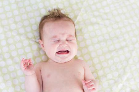 Photo pour Little crying newborn baby on a green blanket - image libre de droit