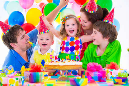 Foto de Happy family celebrating kids birthday. Parents and three children celebrate together. Child party with baloon decoration, cake with candles and present boxes. Celebration for baby boy, toddler girl and school kid. - Imagen libre de derechos