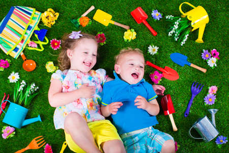 Foto de Kids gardening. Children with garden tools. Child with watering can and shovel. Little kid watering flowers. Girl and baby boy relaxing on green backyard lawn in summer. - Imagen libre de derechos