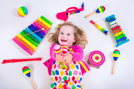 Photo pour Child with music instruments. Musical education for kids. Colorful wooden art toys for kids. Little girl playing music. Kid with xylophone, guitar, flute. - image libre de droit
