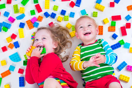 Photo pour Child playing with colorful toys. Little girl and baby boy with educational toy blocks. Children play at day care or preschool. Mess in kids room. View from above. - image libre de droit