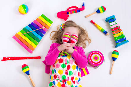 Foto de Child with music instruments. Musical education for kids. Colorful wooden art toys for kids. Little girl playing music. Kid with xylophone, guitar, flute. - Imagen libre de derechos