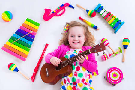 Photo for Child with music instruments. Musical education for kids. Colorful wooden art toys for kids. Little girl playing music. Kid with xylophone, guitar, flute. - Royalty Free Image